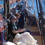 Two schooner crew learning to tie a bowline on the fore deck.