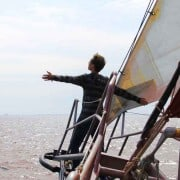 Crewman taking in the sea air over the bowsprit whilst under sail