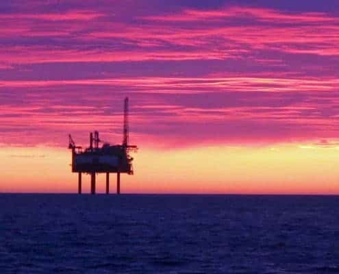 n oil rig offshore in the North Sea at sunset.