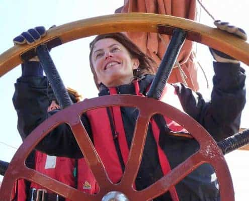 A new sailor takes the wheel of a Tall Ship. Schooner Trinovante, Orkney Sailing Holiday.