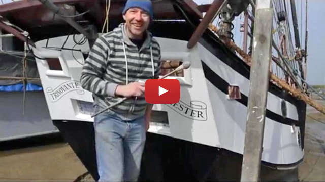 A signwriter hand paints the name on the schooner Trinovante - video image link.