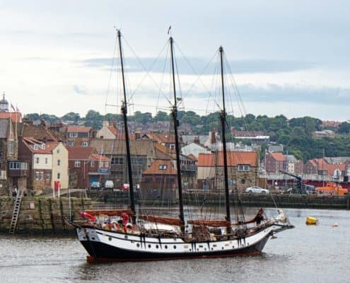 The Schooner Trinovante enters Whitby Harbour on a UK Sailing Holiday. Copyright Alan Green.