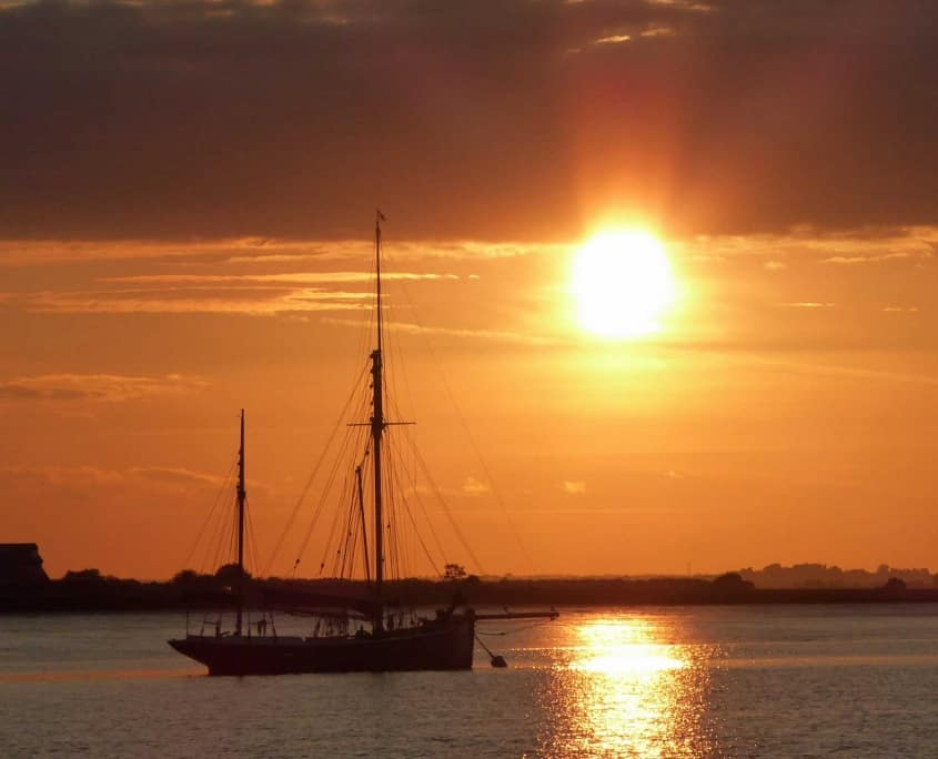 At the end of a Uk Sailing Weekend a traditional sailing boat lies at anchor, sunset Pyfleet creek, Essex, UK