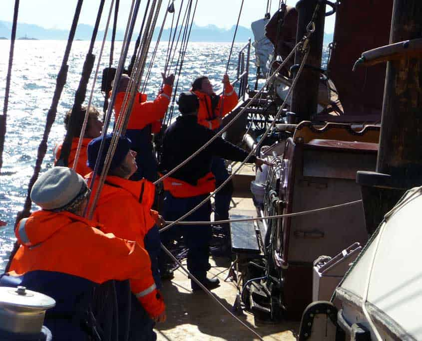 Schooner crew hoisting a topsail on a sailing holiday in Norway