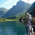 Jumping off the bowsprit in Norwegian fjord. Wet suit recommended