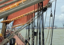 A view of Felixstowe Port through the booms of a sailing ship