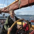 Helming a three masted schooner on a sailing holiday in Norway
