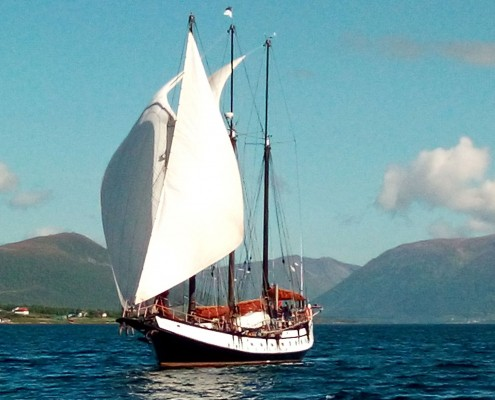 A three masted schooner under light canvas sailing in the Norwegian fjords