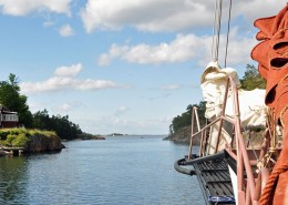 The schooner Trinovante sailing amongst small islands, bowsprit view.