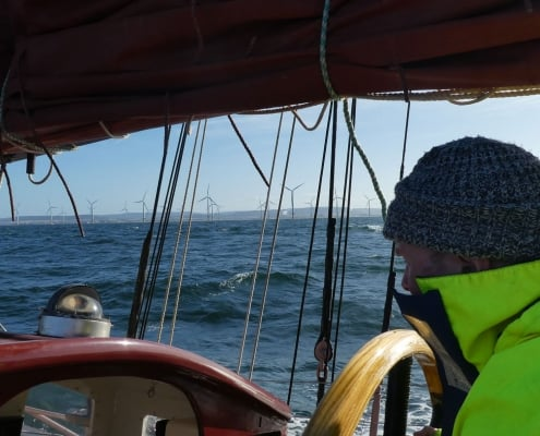 At the helm of a schooner with an offshore windfarm in the background