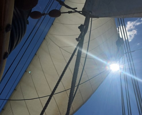 Sunlight streaming round the edge of a jib on a schooner.