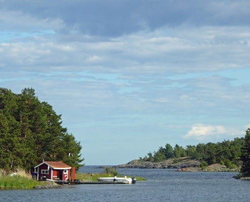 A view of water, trees a red hut and a boat in the Swedish Islands