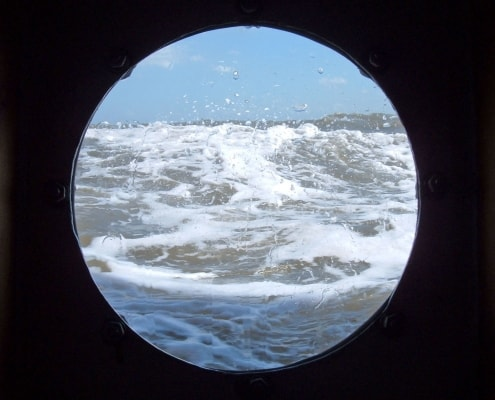 The sea through a round port hole on a sailing ship