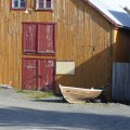 A traditional Norwegian wooden shed with a clinker built skiff in the foreground