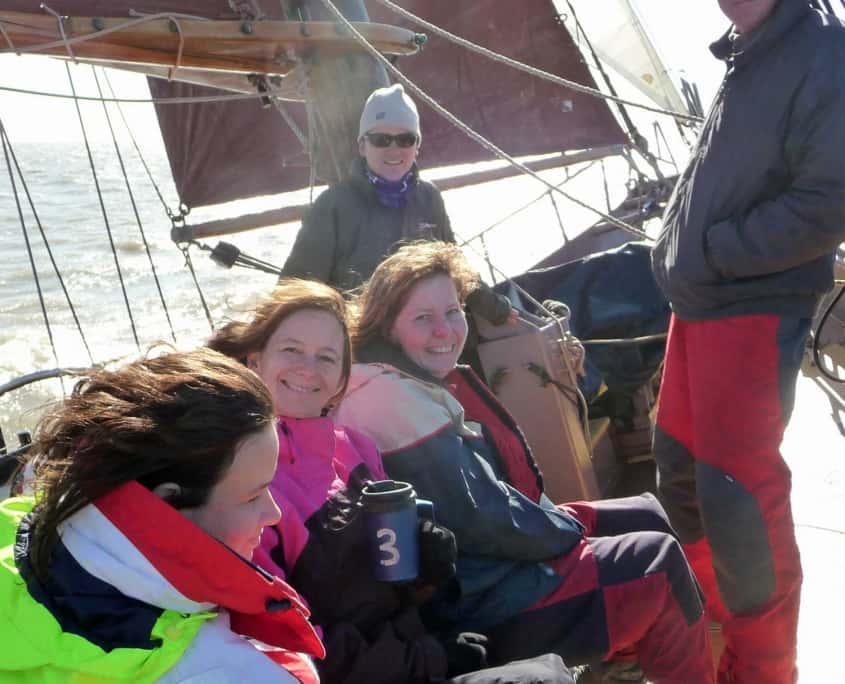 UK tall ship sailing holiday guests being the crew on a schooner. Drinking tea on deck.