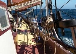 Gaff sail booms on a schooner at sea on a sailing holiday in the UK to Brixham.