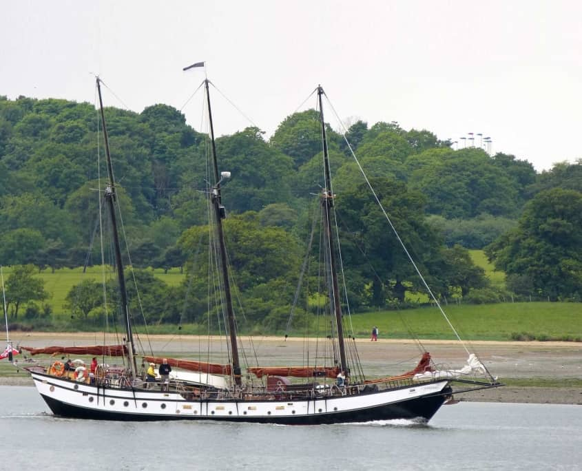 The schooner Trinovante Motors down the river Orwell at the start of a sailing holiday in the UK.